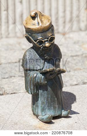 WROCLAW - POLAND, JUNE 12, 2017 : Wroclaw dwarf, small fairy-tale bronze figurine on the side walk,  Wroclaw, Poland. There are over 350 dwarfs spread all over the city, they are a big tourist attraction