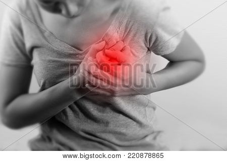 Woman is clutching her chest, acute pain possible heart attack. black and white photo