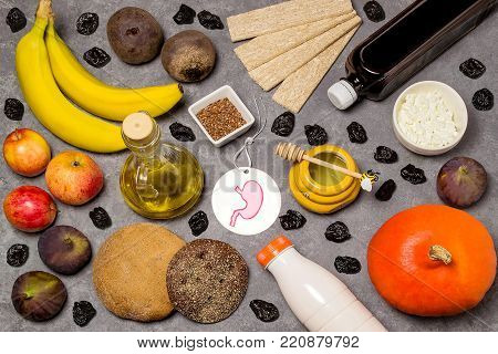 Food products useful for stomach. Set of natural food products are sources of vitamins and minerals. Tag with homemade application from paper - symbol of stomach. Top view