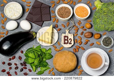 Food is source of vitamin B2. Various natural food rich in vitamins. Useful food for health and balanced diet. Prevention of avitaminosis. Small cutting board with name of vitamin B2. Top view