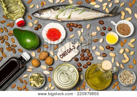 Products - source of fatty acids Omega-3. Set of natural food products rich in fatty acids Omega-3. Useful food for healthy and balanced diet. Small cutting board with word Omega-3. Top view