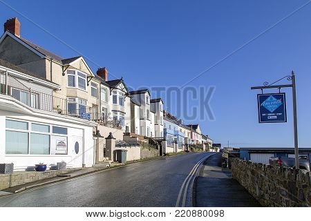 Amroth, UK: January 01, 2018: The main street through the quaint seaside village of Amroth with pastel painted bed and breakfast hotels. Double yellow lines prevent parking on the narrow road.
