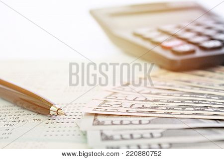 Business, finance, investment or money exchange background concept : American dollars cash money, calculator and savings account passbook or financial statement on table