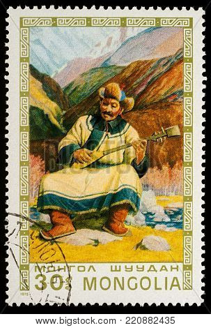 Moscow, Russia - January 06, 2018: A stamp printed in Mongolia, shows Mongolian old man playing lute on mountain background, series
