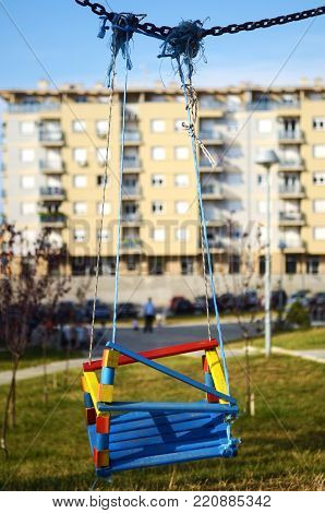 Empty swings in the playground in front of building