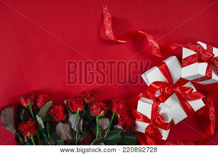 Top view fresh red rose flower and gift box on red deck with empty space for design. For love or valentine day concept. Top view. Copy space. Still life. Flat lay