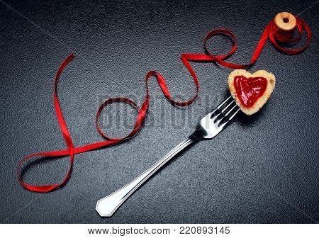 Inscription, word love of red satin ribbon and heart of toast bread with red jam on fork.Valentine day background.Love concept.On dark stone background.Creative.Love background