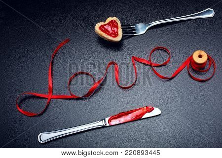 Inscription, word love of red satin ribbon and heart of toast bread with red jam on fork and knife with jam.Valentine day background.Love concept.On dark stone background.Creative.Love background