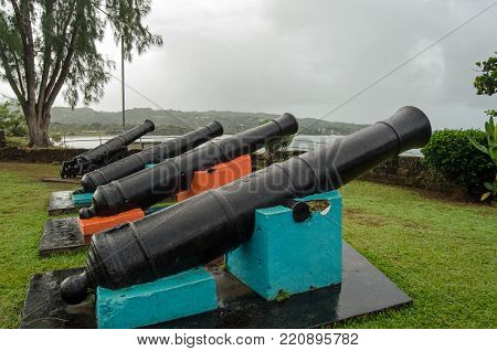Historic cannon pointing out to sea at the eighteenth century Fort James on the Caribbean coastline of Tobago, Trinidad and Tobago.  The fort was used by a number of settlers including French and British and is sited at the town of Plymouth. Rainy morning