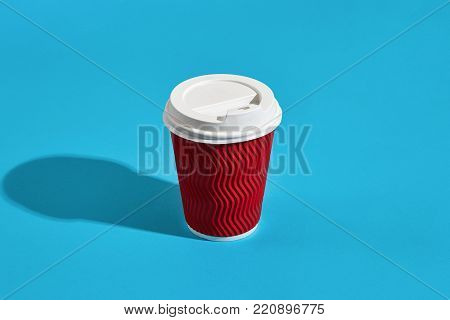 Hot coffee in red paper cup with white lid on blue background with shadow, blurred and soft focus image. Still life. Copy space