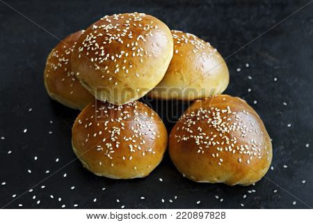 Crispy buns with sesame seeds on a black background
