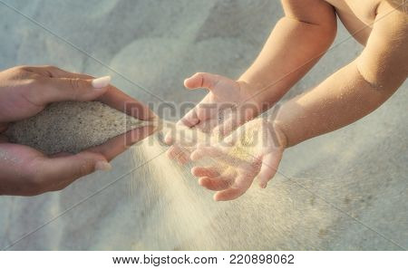 Mother and small baby play with sand slipping through woman hand fingers. Summer vacations with children.
