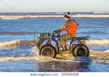 Kijkduin, The Hague, the Netherlands - 7 January 2017: quad biker doing topographic beach survey