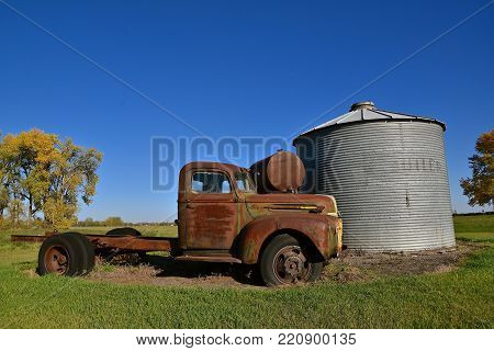 EAST GRAND FORKS, MINNESOTA, October 7, 2017: The rusty Ford  truck parked by an old grain bin is a product of the Ford Motor Company located in Dearborn, Michigan started by Henry Ford and incorporated on June 16, 1903