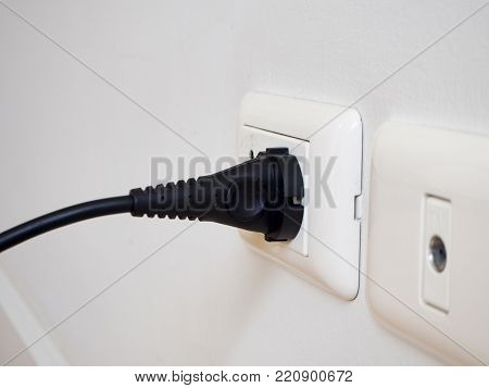 Black electric power plug on white socket on white wall.