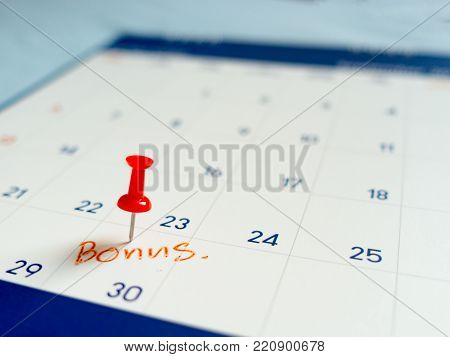 Red pin push on day 30 of end month on white calendar. Mark this day as bonus date.