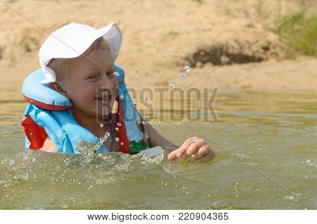A five-year-old boy in a life jacket is bathing in the lake
