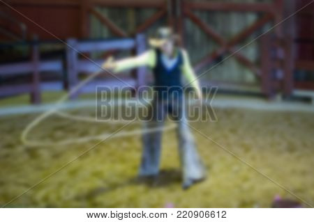Blurred Image - Cowboy spinning lasso for show in park