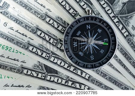 Magnetic compass on pile of dollar bills usning as world economics fortune direction.