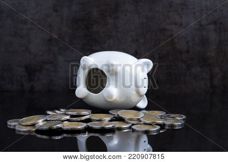 Empty piggy bank lay on dark black table with coins using as broke or personal finance problem crisis.