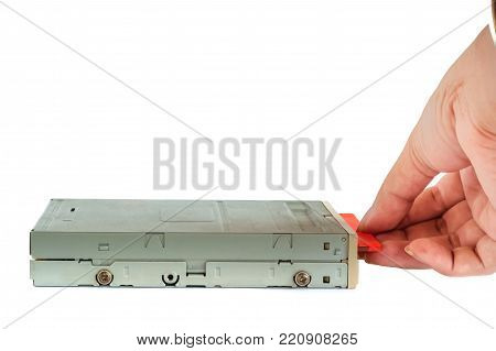 Hand putting the diskette into the floppy disk drive on white background, old technology and legacy industrial computer equipment