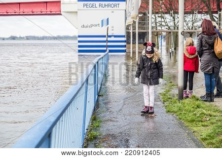 DUISBURG , GERMANY - JANUARY 08 2017 : Little girl surprised by the river Rhine flooding the promenade in Ruhrort