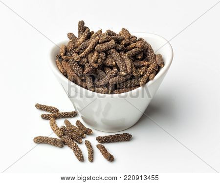 Long pepper or piper longum in white bowl isolated on white background.