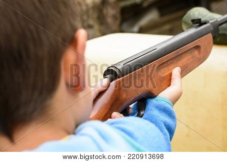 A boy shooting from an air rifle to a target. A boy with a gun in his hand. Shooting training from a gun. Dangerous game of little boy.