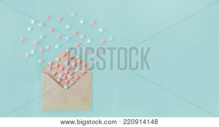 Multicolor sweets sugar candy hearts fly out of craft paper envelope on the light blue background . Valentine day. love concept. Gift, message for lover. Space for text. Wide banner