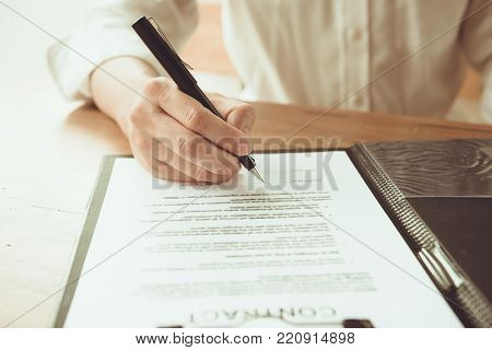 Close-up Of Businessperson Signing Contract, man writing paper at the desk with pen and reading book at table with basic business Form document working in office