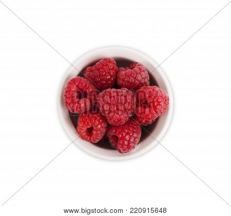 Raspberries in a wooden bowl isolated on white background. Vegetarian or healthy eating. Juicy and delicious raspberry with copy space for text. Top view.