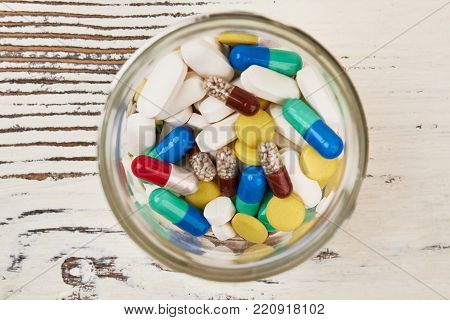 Pills in a glass jar. Heap of diverse medical drugs: tablets, caplets and capsules. Modern medicine, cure for diseases.