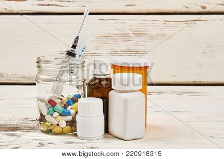 Medications and syringe on wooden table. Different pills and syrups. Enhance and support immunity. Medical background.