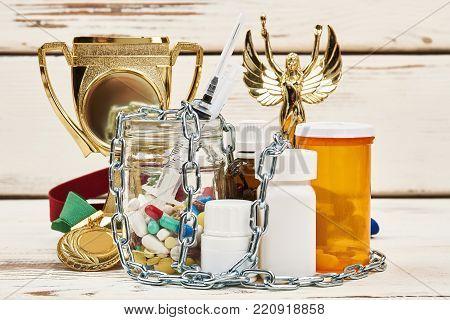Championship trophy and illegal medications. Chains on bottles of pills and syringe. Doping scandal concept.
