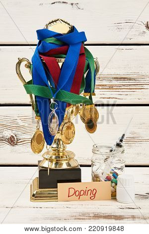 Medals, trophy and doping drugs on wooden table. Multiple winner caught cheating. Sport and disqualification.