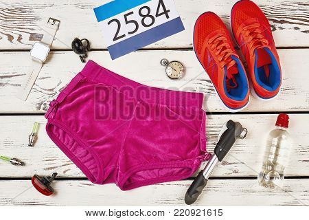 Participant's number, shorts and sneakers. Bicyclist's equipment, water and smart watch on rustic table. Prepare for cycling race. poster
