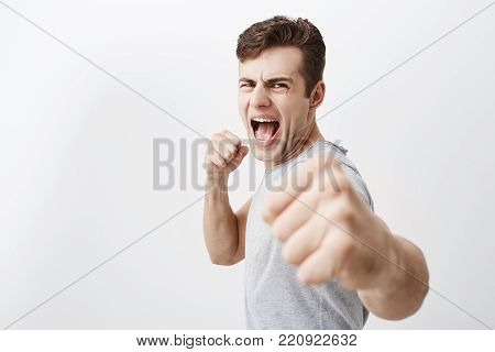 Furious outraged caucasian man shouts in anger, frowns his face, keeps fists, going to defend himself in fight with criminals. Desperate european guy dark hair shows his power, clenches fists.