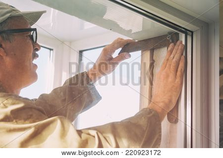 Carpenter makes measurements when installing the window