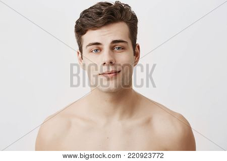 Naked positive caucasian male with pure healthy skin and dark hair, appealing blue yes, smiles gently as being glad after date with grifriend. Beauty and youth concept.