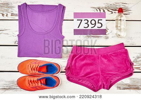 Athlete's uniform for running race. Comfy sneakers, shorts, shirt, bottle of water and participant's number. Sports flat lay shot.