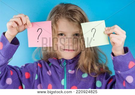 Girl holding stickers with a question marks