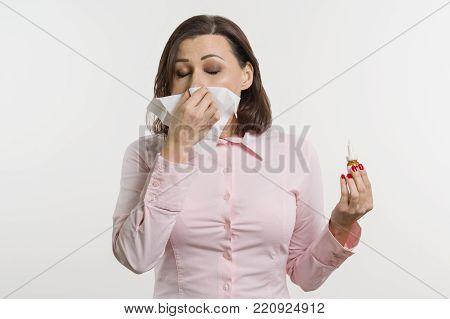 Sick woman holding a handkerchief and nasal spray.
