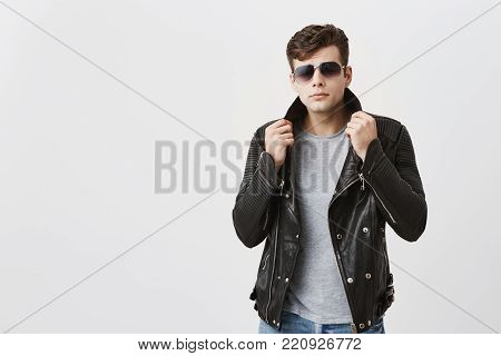 Muscular confident male wearing sunglasses posing indoors against gray background. Attractive handsome caucasian guy with trendy haircut in black leather jacket and jeans, pulling with hands jacket up, looking with appeal at camera