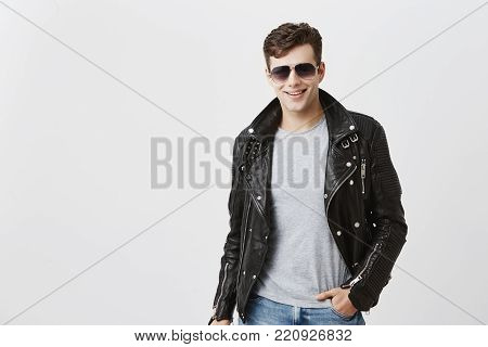 Caucasian male model with appeal look, smiling broadly with white even teeth, posing indoors against gray background. Stylish handsome attractive European young man with trendy haircut dressed in black leather jacket and gray t-shirt, wearing sunglasses.