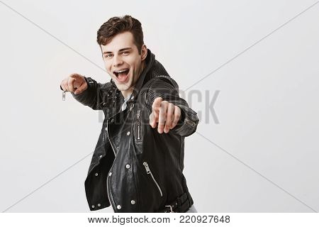 Stylish happy caucasian male wears black leather jacket over gray t-shirt, broadly smiling, demonstrating his white teeth, points at camera with fore fingers, chooses someone, has joyfull expression, rejoices success and good luck during day. Joy and happ