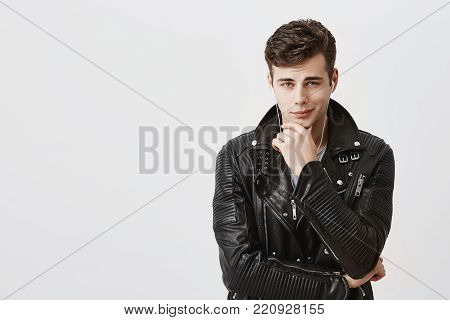 Portrait of suspicious pensive young caucasian male in stylish black leather jacket touching face while thinking over something, trying to come up with solution, having perplexed and puzzled expression. Face expression
