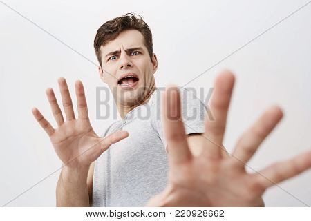 Caucasian man with scared expression on his face making frightened gesture with his palms as if trying to defend himself from someone. Fearful european young male asking to stop, gesturing with his hands