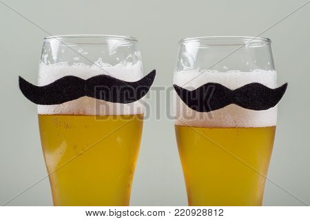 Two glasses with beer and a symbolic mustache. Background grey wall