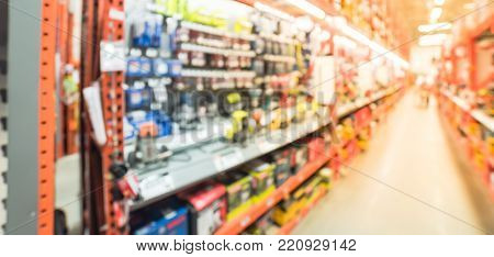 Blurred large hardware store in America. Defocused interior home improvement retailer, racks of various power tools, cordless kit router, sander, cordless drills and building material. Panorama style. poster