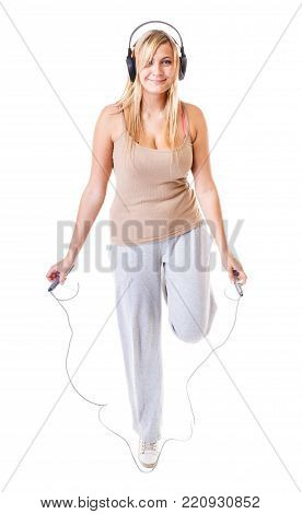 young sporty girl plus size doing exercise with jump rope while listening music. Weight loss concept. Fitness woman isolated on white